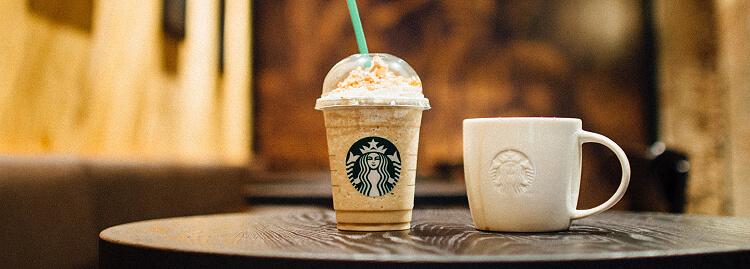 Copo e xícara com identidade visual da Starbucks em cima de uma mesa